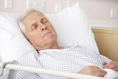 Senior man asleep in hospital bed Stock Photos