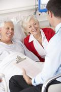 Stock Photo of Doctor talking to senior couple on UK Hospital ward