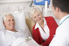 Stock Photo of Doctor talking to senior couple on USA Hospital ward