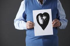 Senior man holding ink drawing of heart - stock photo