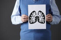 Senior man holding ink drawing of lungs - stock photo