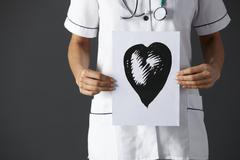 American nurse holding ink drawing of heart - stock photo