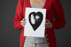 Senior woman holding ink drawing of heart - stock photo