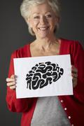 Stock Photo of Senior woman holding ink drawing of brain