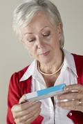 Senior woman looking at prescription drug pack - stock photo