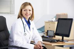 Portrait American doctor sitting at desk - stock photo