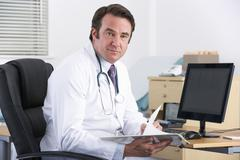 Portrait UK doctor sitting at desk Stock Photos