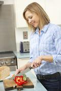 Woman chopping vegetables in domestic kitchen Stock Photos