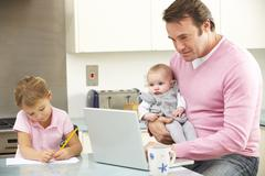 Father with children using laptop in kitchen - stock photo