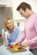 Mature couple preparing meal in domestic kitchen - stock photo