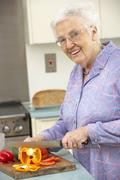 Senior woman chopping vegetables in domestic kitchen - stock photo
