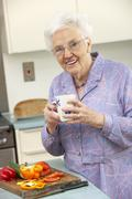 Senior woman preparing food in domestic kitchen - stock photo