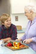 Grandmother and grandson preparing food in kitchen Stock Photos