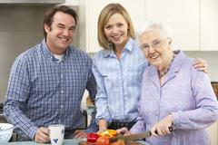 Senior woman and family preparing meal together - stock photo