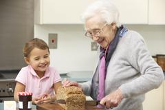 Grandmother and granddaughter preparing food in kitchen Stock Photos