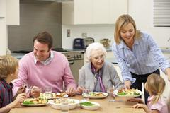 Multi-generation family sharing meal together - stock photo