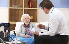 UK GP visiting senior woman at home Stock Photos