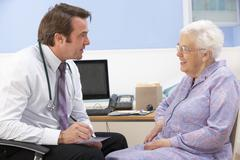 UK GP talking to senior woman patient Stock Photos