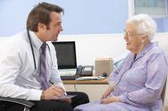 Stock Photo of UK GP talking to senior woman patient