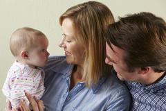 Studio Shot Of Happy Family With Baby - stock photo