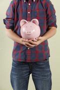 Cropped Studio Shot Of Young Boy Holding Pink Piggy Bank Stock Photos