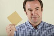 Stock Photo of Studio Shot Of Middle Aged Man Holding Wage Packet