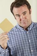 Studio Shot Of Middle Aged Man Holding Wage Packet Stock Photos