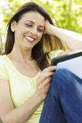 Woman using tablet outdoors - stock photo