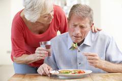 Senior woman looking after sick husband - stock photo