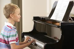 Young boy playing grand piano at home - stock photo