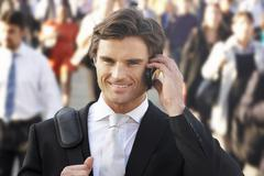 Male commuter in crowd using phone Stock Photos
