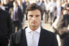 Male commuter in crowd wearing headphones Stock Photos
