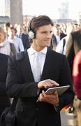 Male commuter in crowd with tablet and headphones Stock Photos