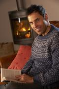 Middle Aged Man Relaxing With Book By Cosy Log Fire Stock Photos