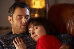 Middle Aged Couple Cuddling On Sofa By Cosy Log Fire Stock Photos