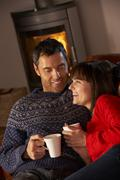 Middle Aged Couple Sitting On Sofa By Cosy Log Fire With Hot Drink - stock photo