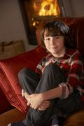 Young Boy Sitting On Sofa By Cosy Log Fire Stock Photos