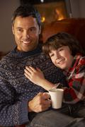 Father And Son Relaxing With Hot Drink Watching TV By Cosy Log Fire Stock Photos
