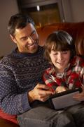 Father And Son Using Tablet Computer By Cosy Log Fire - stock photo