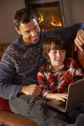 Father And Son Using Laptop Computer By Cosy Log Fire - stock photo