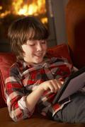 Young Boy Relaxing With Tablet Computer By Cosy Log Fire Stock Photos