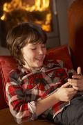 Young Boy Relaxing With MP3 Player By Cosy Log Fire - stock photo