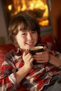 Young Boy Relaxing With Hot Drink By Cosy Log Fire - stock photo