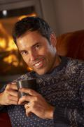 Middle Aged Man Relaxing With Hot Drink By Cosy Log Fire - stock photo
