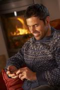 Middle Aged Man Using MP3 Player By Cosy Log Fire - stock photo