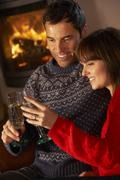 Middle Aged Couple Sitting Sofa By Cosy Log Fire With Glass Of Champagne Stock Photos
