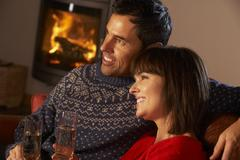 Middle Aged Couple Sitting Sofa By Cosy Log Fire With Glass Of Champagne - stock photo