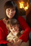 Mother And Daughter Relaxing On Sofa By Cosy Log Fire - stock photo