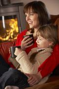 Mother And Daughter Relaxing With Hot Drink Watching TV By Cosy Log Fire - stock photo
