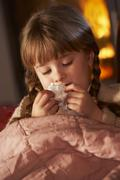 Sick Girl With Cold Resting On Sofa By Cosy Log Fire - stock photo